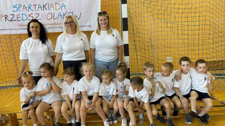 Na zdjęciu widać uczniów wraz opiekunami na zawodach w białych koszulkach.